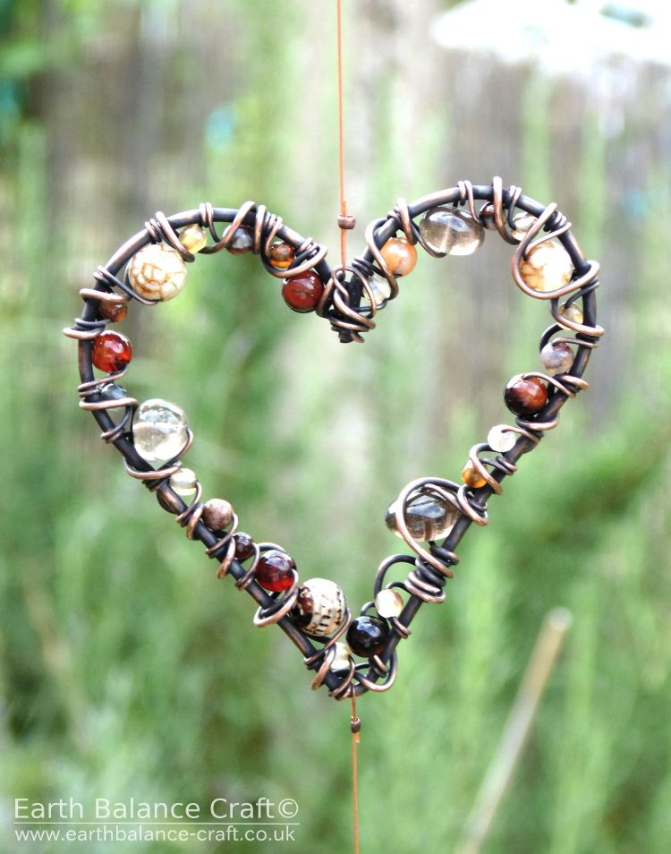 This sun catcher has three heart shaped hanging ornaments made from copper wire wrapped with agate and quartz beads. This little piece of wall art is suitable for the home and garden. The design was inspired by an earthy woodland colour palette, muted and harmonious tones of browns and black with hints of red and copper. A hand crafted piece made by Nicola Jones, based in Horsham, West Sussex.