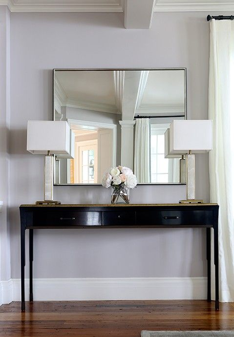 Chic Foyer Features A Glossy Black Console Table With Black Pulls Accented With A Gold Top