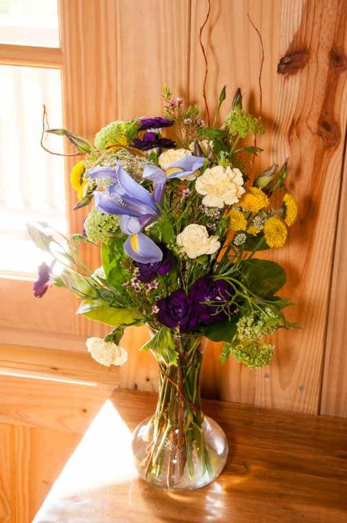 sign-in table arrangement, purple  and yellow carnations, yellow buttons, queen Anne's lace, Lavender Iris, and green viburnium
