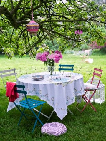 Summer garden table setting under a tree with paper lanterns hanging in a tree & Summer garden table setting under a tree with paper lanterns hanging ...