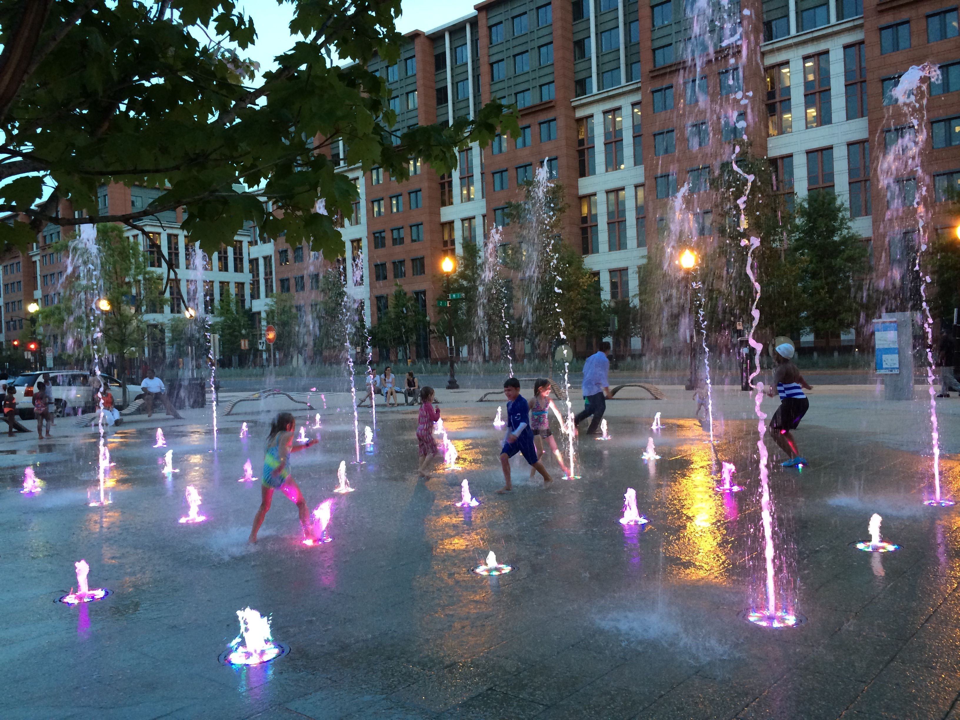 urban splash pad with colored lights around the fountain jets ...