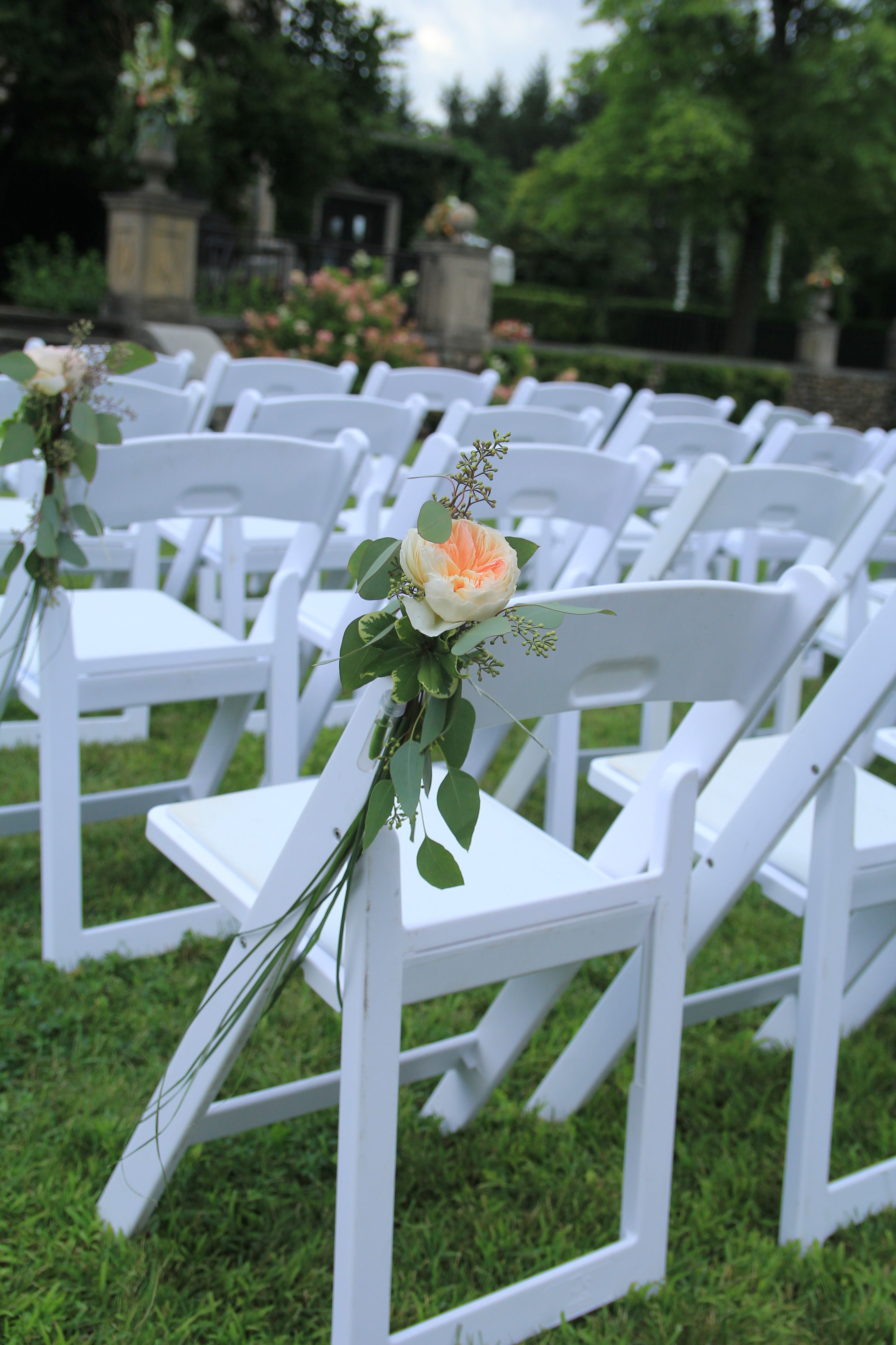 gorgeous simple decoration for a garden chair at an outdoor wedding ceremony.