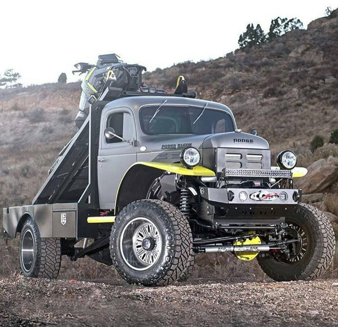 Custom flatbed dodge powerwagon with a custom snowmobile ramp on the back