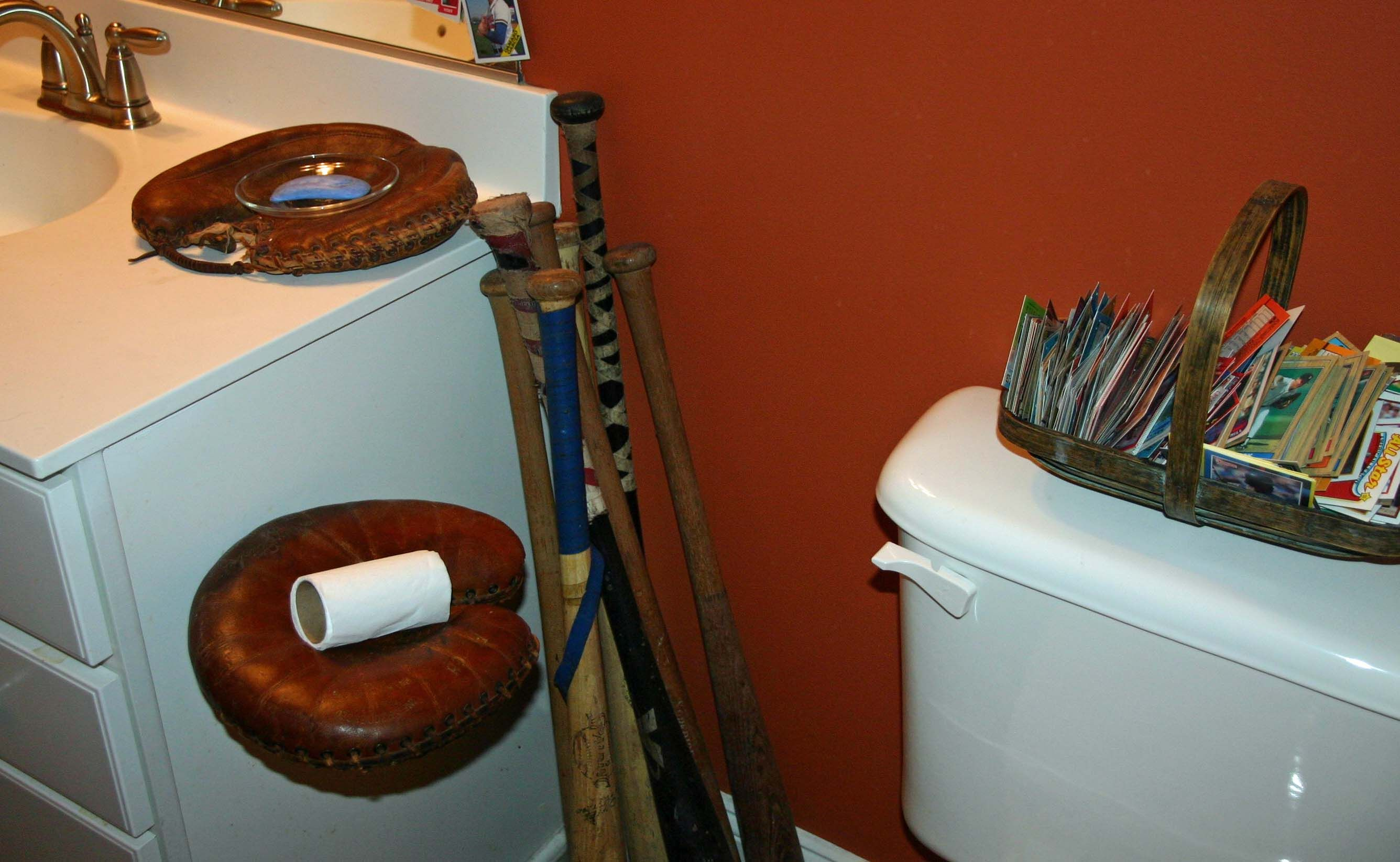 Created a toilet paper holder out of a baseball catcher 39 s for Baseball bathroom ideas