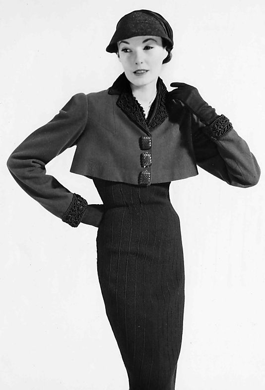 * Jacket wool, silk, ceramic  spring 1938 Elsa Schiaparelli (1890–1973) This jacket was designed for Schiaparelli's spring 1938 collection. The silhouette, particularly the curved seaming of the back, is reminiscent of the spencer jacket worn in the early 19th century. The buttons and the dense cord embroidery are an example of Schiaparelli's desire to use trim and decoration that was unusual