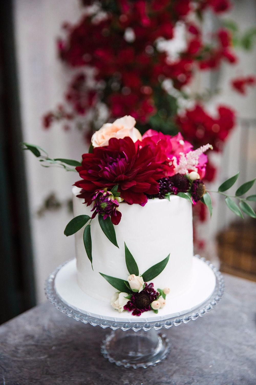 Sweetheart wedding cake with red pink and peach florals wedding
