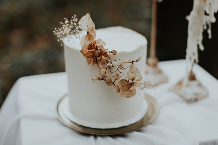 A single tier white wedding cake with dried flowers | Beautiful woodland wedding styled shoot with cranberry red accents | fabmood.com #wedding #woodlandwedding #cranberrywedding #autumnwedding #woodland #cozywedding