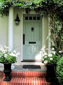 Door color + evergreens with white blooms in front landscaping