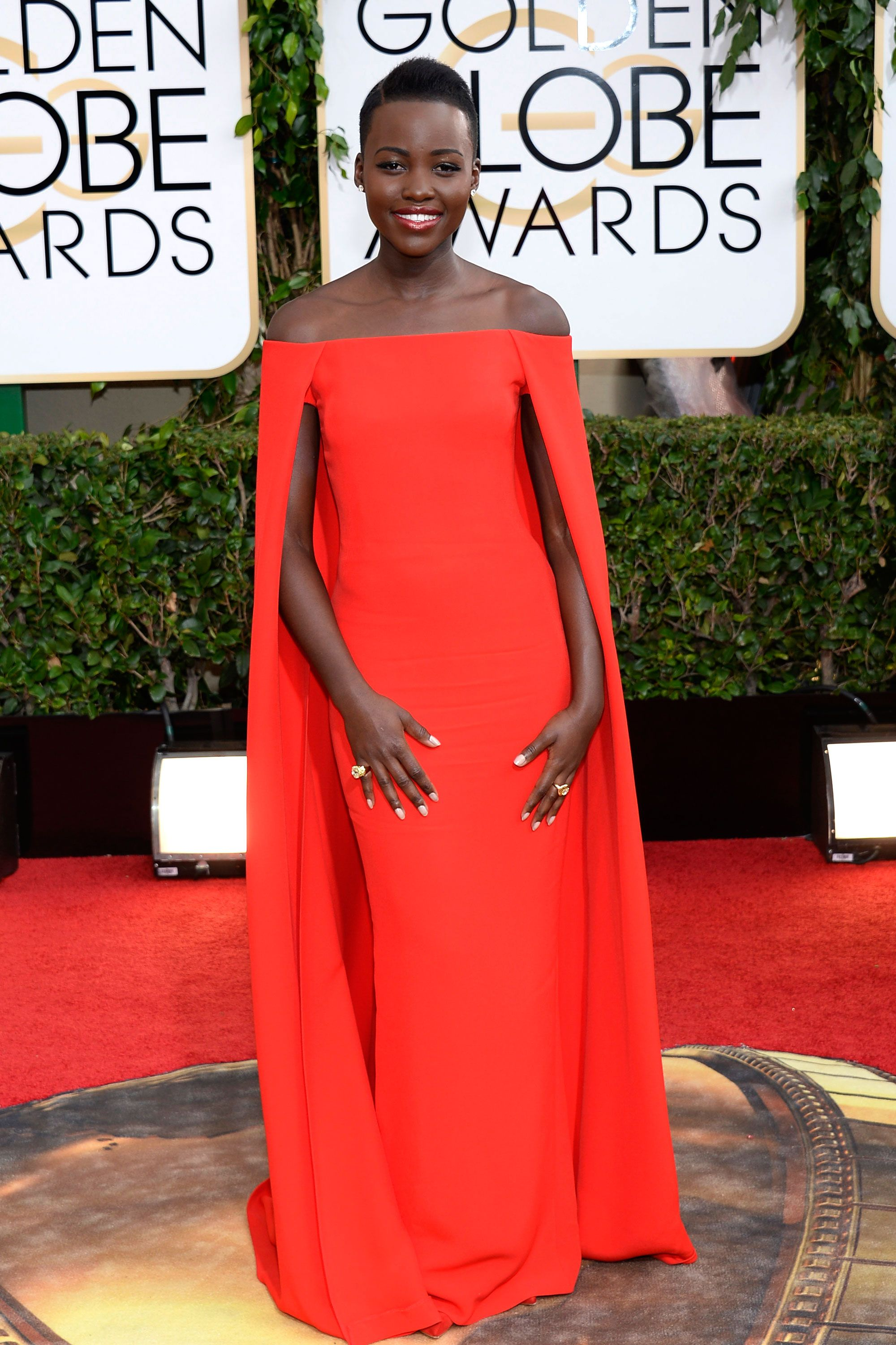 Lupita N'yongo. Absolutely stunning Ralph Lauren gown on an incredibly beautiful woman.  I would normally want to see jewels, but she is perfect with just diamond studs, anything else would detract from the architecture of the dress.