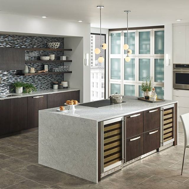 A glittery backsplash, a dark wood finish, and a calm tone of #Viatera #Aura waterfall countertop bring this modern kitchen to another level! //Featured design: Aura    #Viatera #Quartz #quartzcountertop #design #interiordesign #designideas #homedesign #instahome #instapic #showroom #instapic #LGHausys #inspiration #interior #kitchen #kitchendesign #floral #gold #countertop #aura #backsplash #waterfallcountertop