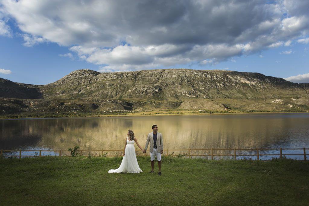 Paula com seu lindo vestido de noiva  de mãos dadas com Bruno estiloso de bermuda e terno, ao fundo a linda paisagem da Lapinha da Serra