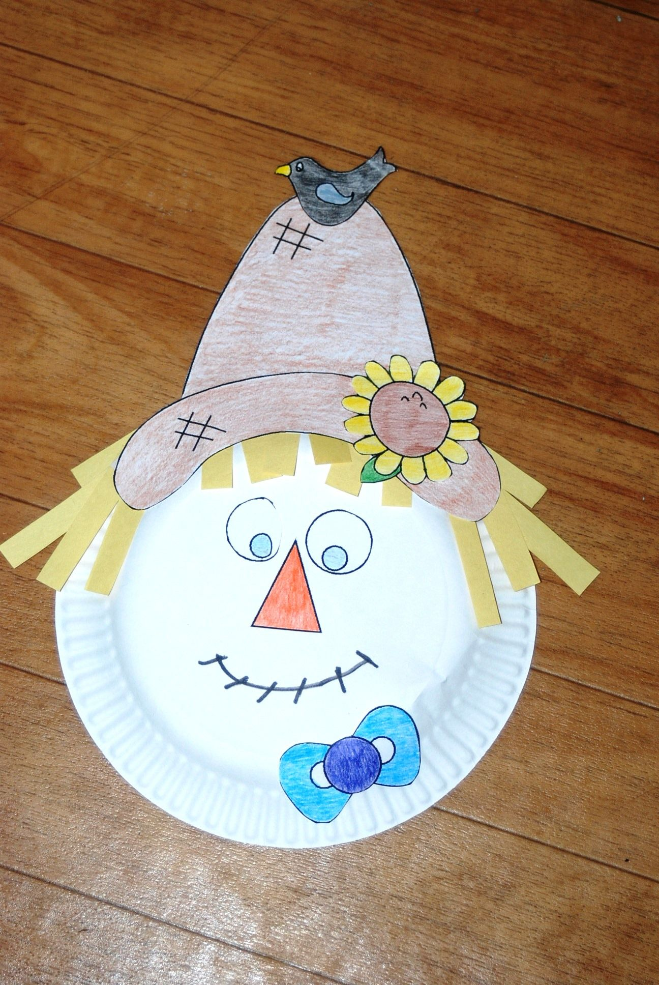 paper plate scarecrow • cut out hands and hat and glue to plate • cut and glue strips of yellow construction paper for hair • glue wiggle eyes, cut out nose and draw the rest of the face.