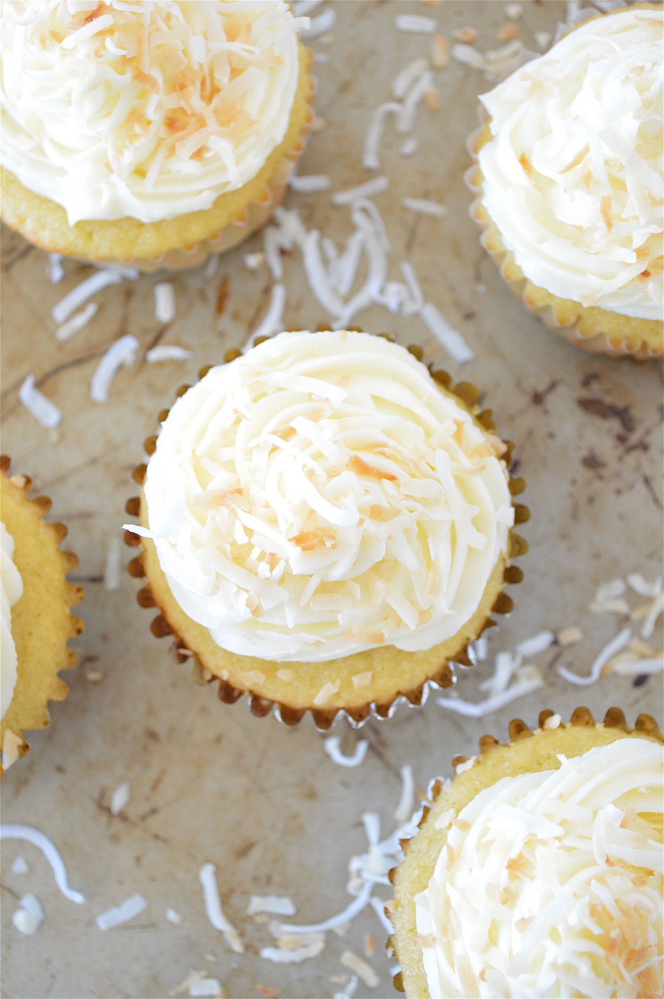 Gluten-Free Coconut Cream Pie Cupcakes - super moist, gluten-free, vanilla pudding stuffed cupcakes made with coconut flour AND topped with a vanilla and coconut flavored frosting!