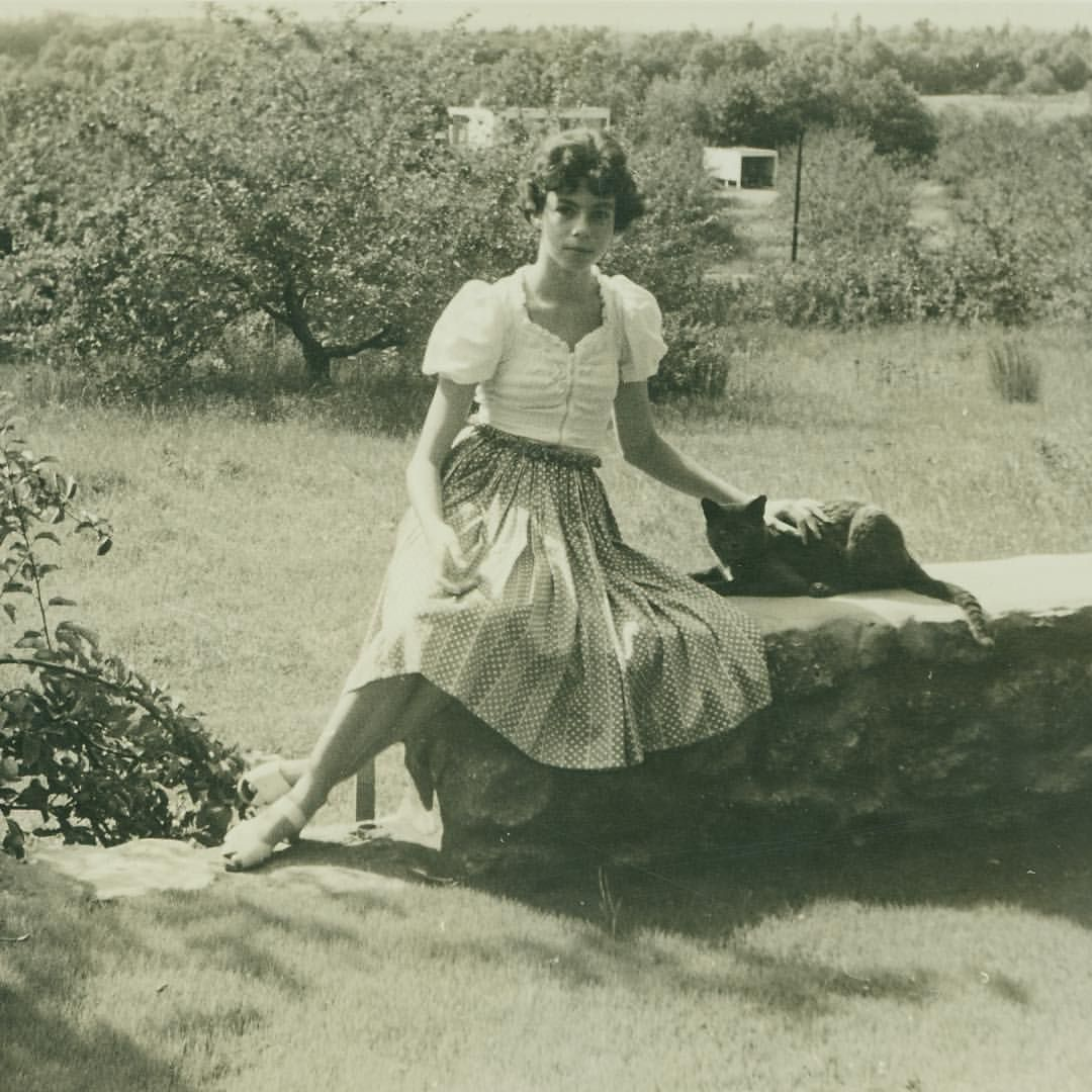 Ati Gropius sitting on a stone wall at Gropius House with