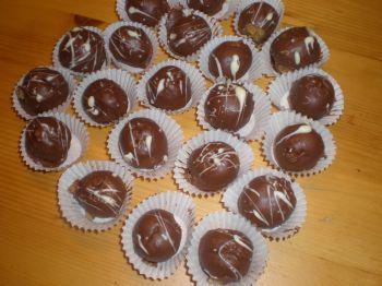 Rumkugeln ohne Schmelze-100 Portionen:400 g Löffelbiskuit,2 EL Marmelade,12 cl Rum (3 Flachmänner),100 g weiche Butter,200 g Zartbitter Schokolade,400 g Schokoladenstreusel.Löffelbiskuit in einen Gefrierbeutel füllen und mit einem Nudelholz hin und her rollen, sodass er fein gemahlen ist.Zartbitter Schokolade fein reiben, zusammen mit Marmelade, Butter, Rum zum Löffelbiskuit geben. Alles gut vermengen.Kugeln formen, diese in den Schokoladenstreusel wälzen.in die Pralinenmanschetten legen.