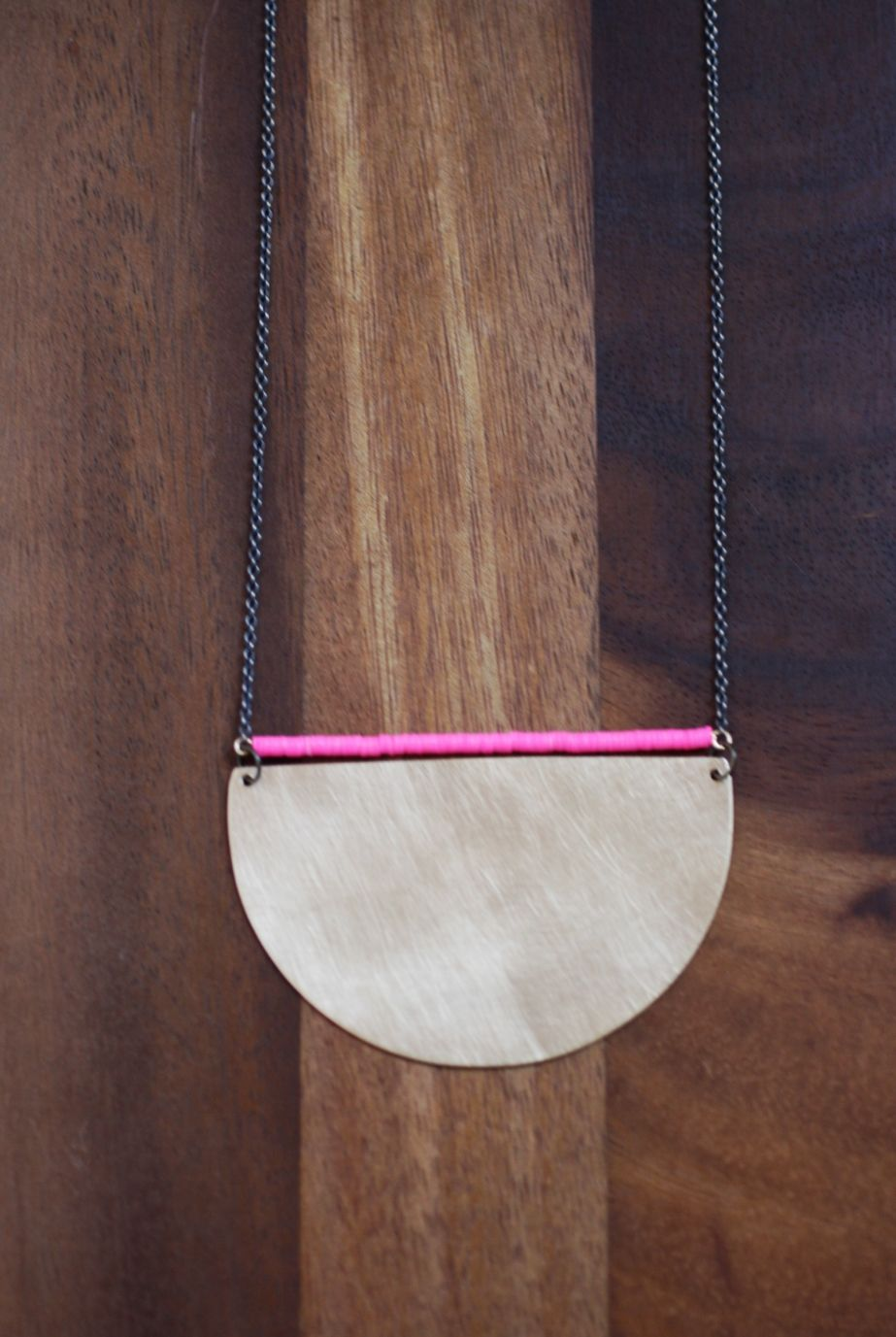 "Matte brass with neon pink heshi beads on an antiqued brass chain.  Pendant: 3"" x 1.75"""