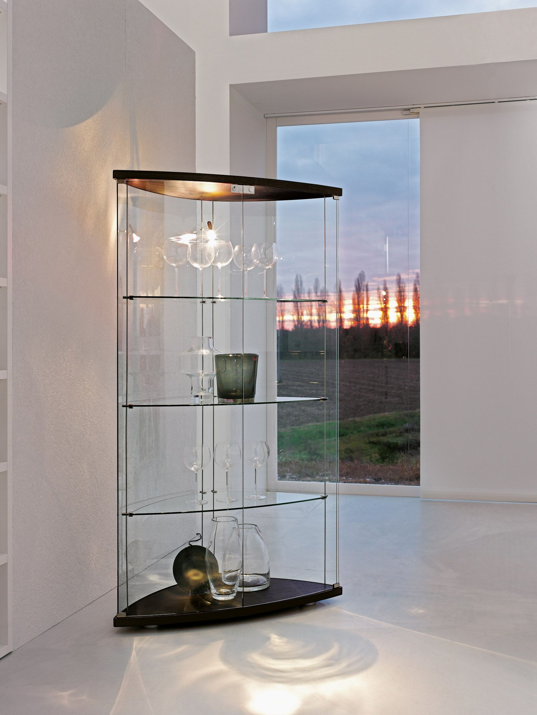 Gracia glass cabinet with doors and back panel in curved glass. Available in different finishing and with internal led light spot. The elegance of curved glass to let your precious glassworks stand out.