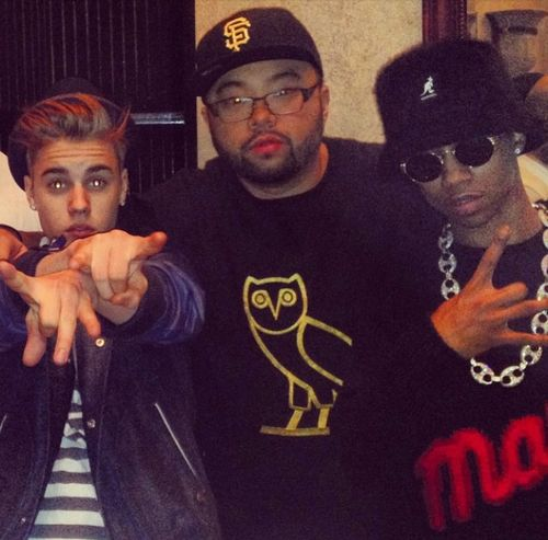 Rapper Lil Twist (young money artist) and friend Justin Bieber both saluting the devil. Bieber pointing his horns at viewer, their friend wearing a shirt with the symbol of Bohemian Grove. Bieber's eyes