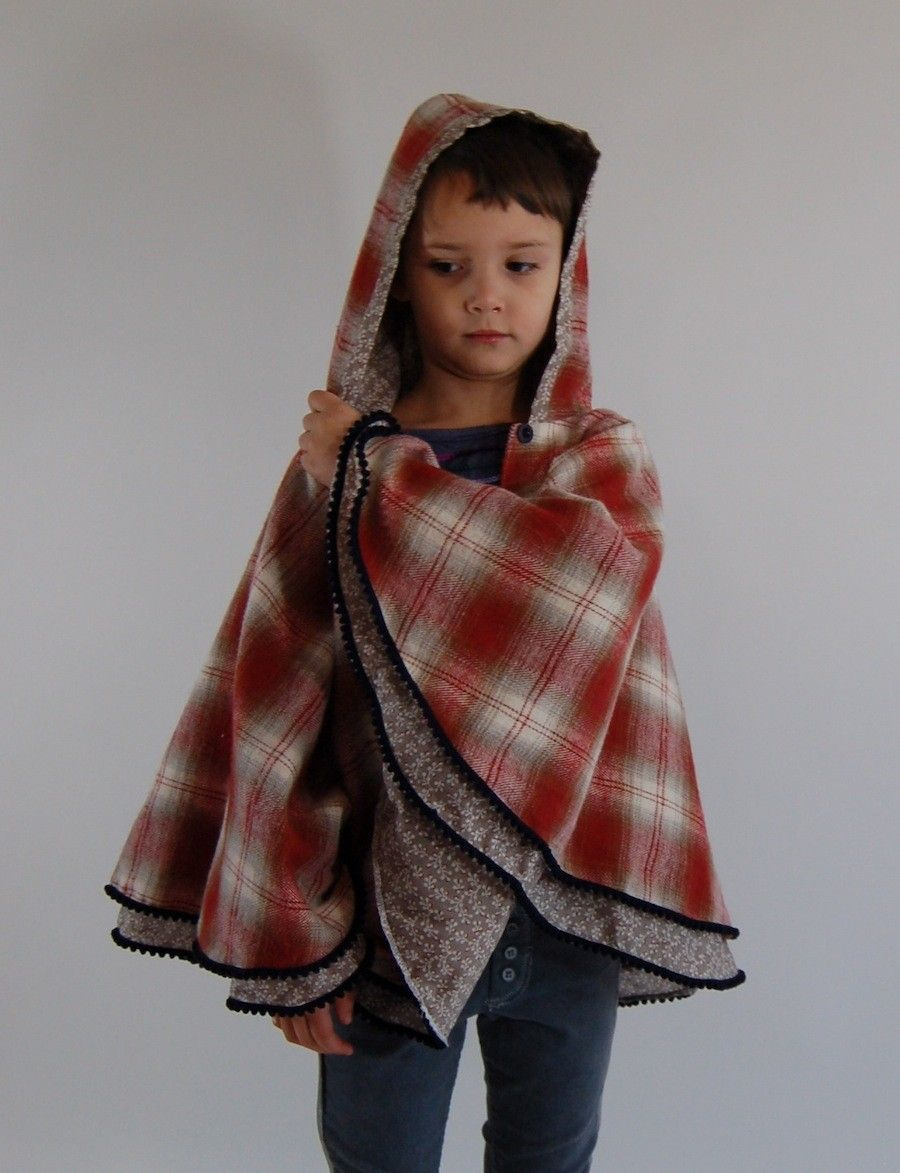 Girl And A Mouse's Plaid Poncho in Brick from Fall 2012, super cute! It's a hooded plaid flannel outer, lined with a soft cotton print and trimmed with navy blue pom poms. One of our favorites!