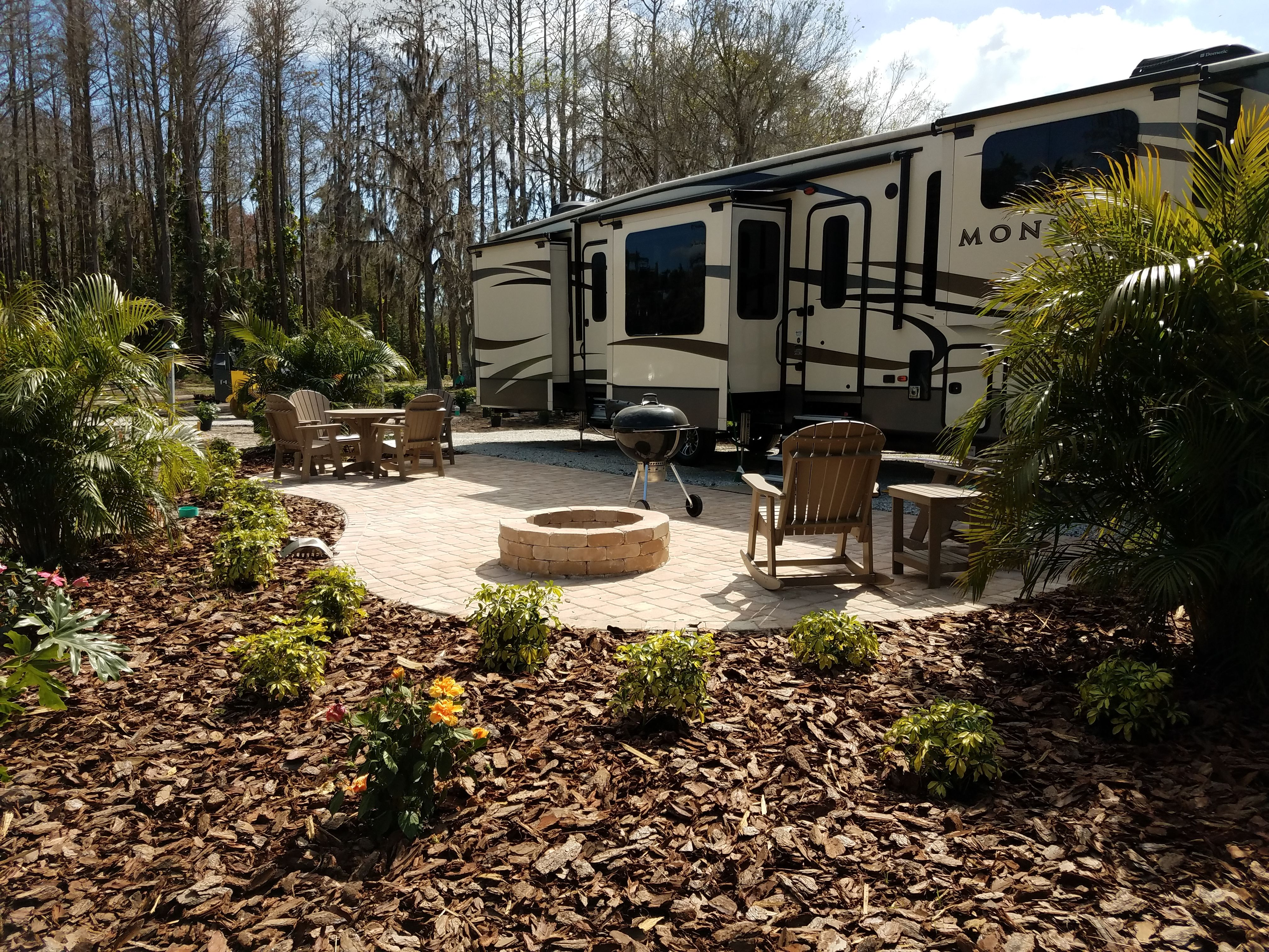 Expansive And Lush Landscaping Surround This Rv Patio Site At The Clearwater Lake Tarpon Koa Rv Lots Recreational Vehicles Backyard