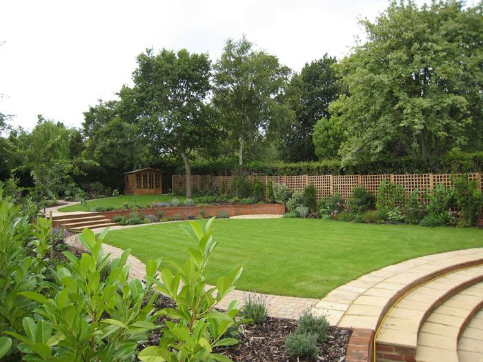 Sloping Garden Contoured Into Comfortably Flat Areas. Curved Steps Rise  From Main Patio To A Large Lawn, With Small Circular Patio Backed By A  Curved Wall.