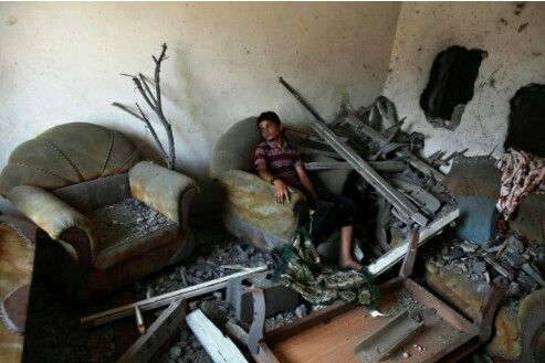 A Palestinian kid sits in his destroyed home in the Shadjlin district of Gaza, bombed by the IDF on 22nd Aug 2014