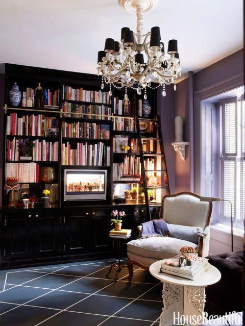 Kaihoi built the floor-to-ceiling bookcase himself and painted it high-gloss Black by Fine Paints of Europe. The floor, painted to mimic a rug, is Hale Navy and White Down, both by Benjamin Moore. Big furniture makes a small room seem grander, says Kaihoi. #EuropeHomeDecorEnglishCottages #europehomedecoration #halenavybenjaminmoore