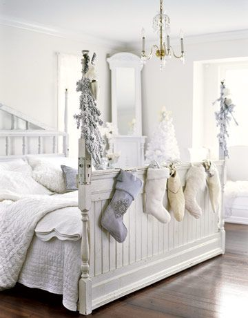 White Christmas decor - stockings hanging from the bed.
