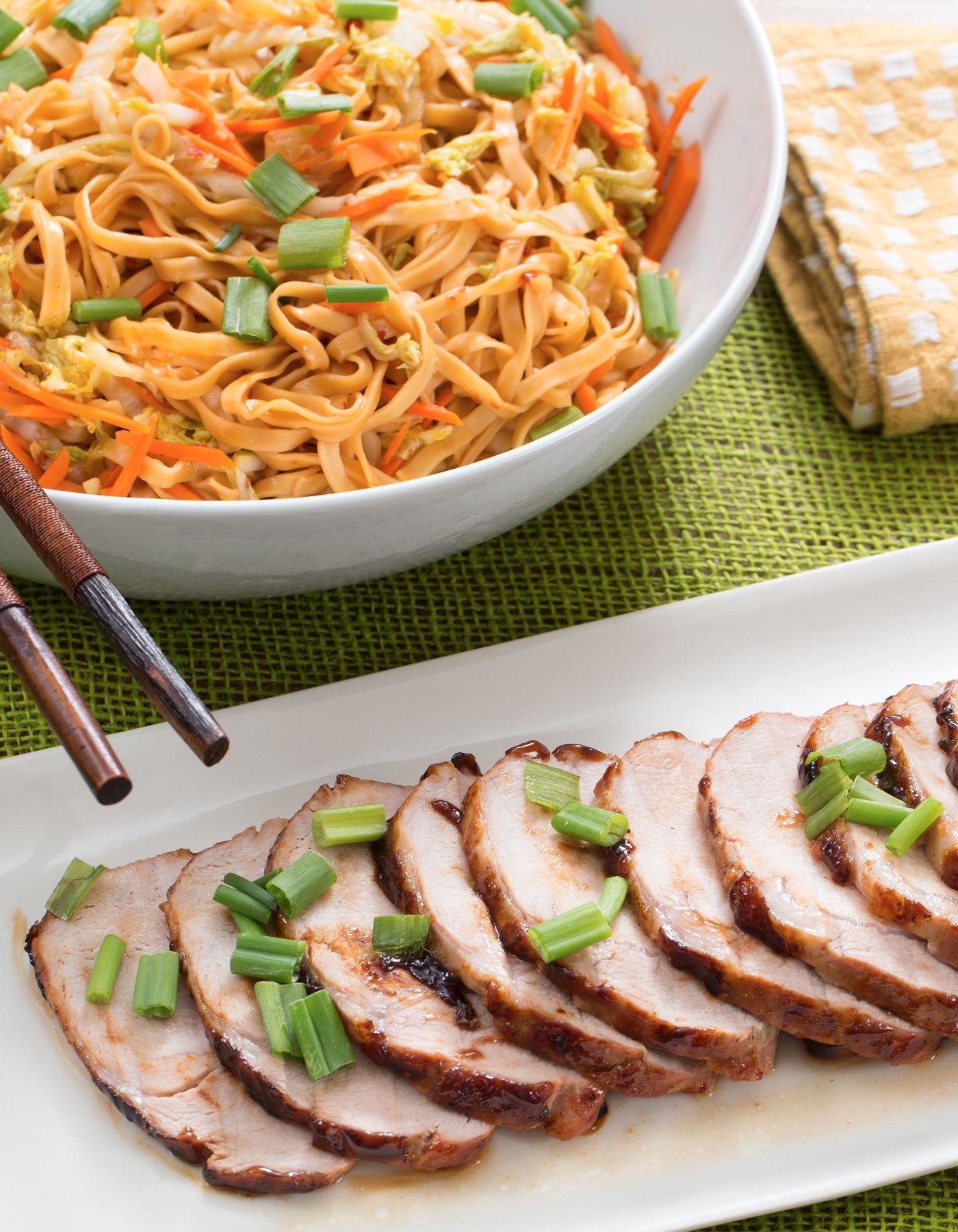First, we're glazing hearty roast pork with hoisin sauce, a citrusy, sweet ingredient used throughout Chinese cooking. Second, on the side, we're dressing fresh wonton noodles with a lime-infused peanut sauce, spiced with a dash of sambal oelek—a Southeast Asian condiment made from red chile peppers.
