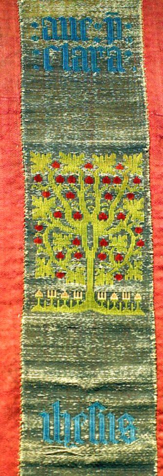 DI 76 (Lüneburger Klöster) Kloster Wienhausen 2. H. 15. Jh.    Signatur: DI 76, Nr. 73    Sogenannte Kölner Borte auf Antependium.1) Ausgestellt im Textilmuseum. Die gewirkte Borte ist in der Mitte eines älteren Textils aus dem 14. Jahrhundert eingefügt, das zweimal sechs rechteckige Felder mit gestickten Darstellungen von Greifenpaaren mit Wappen zeigt. Auf der Borte stilisierte Bäume mit Blüten und Früchten sowie eine sechsblättrige Rosette in der Mitte, dazwischen die Teile der mit blauem…