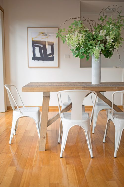 Rustic Timber Dining Table White Metal Chairs Black And Yellow Artwork