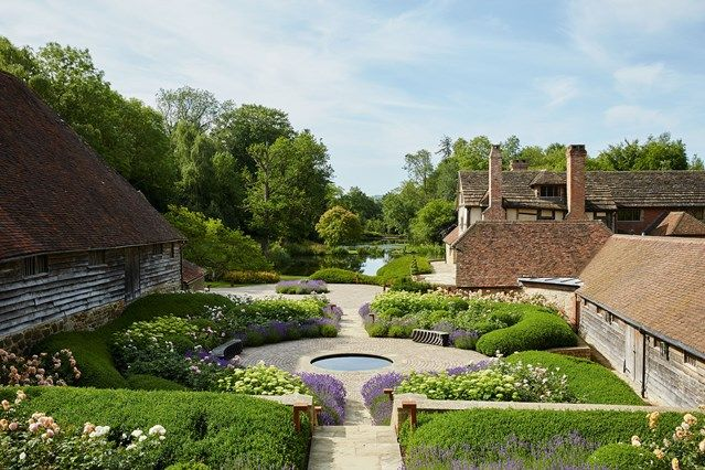 A view of the lake and garden with hedges, lavender and seating areas. Family home in restored and modernised barn in Suffolk – pale and rustic country interiors.