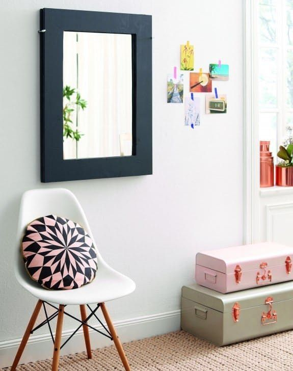 stylish room with eames style shell chair, stacked suitcases, a round patterned pillow and a mirror that folds out to a table