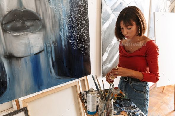 Portrait of young woman using painting tools while drawing in studio by vadymvdrobot. Portrait of young caucasian artistic woman using painting tools while drawing picture in studio #AD #painting, #tools, #woman, #Portrait