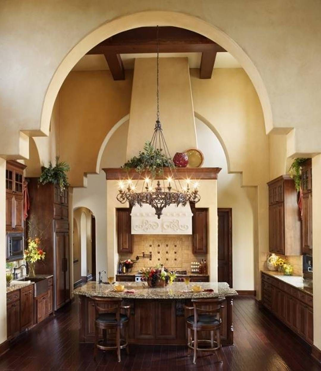 Center Island With Adorable Chandelier In Tuscan Kitchen