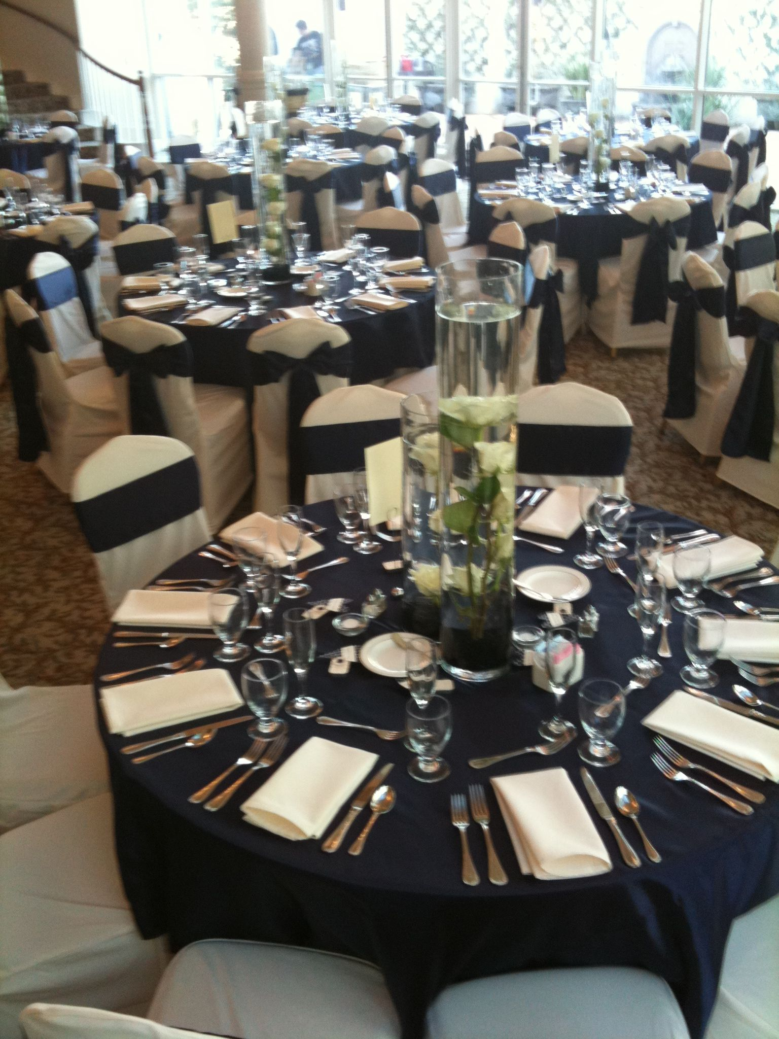 Our Ivory Tablecloth Under Our Satin Navy Overlays With Ivory Chair Covers  And Satin Navy Chair Sashes. Wedding At #ashtongardens .
