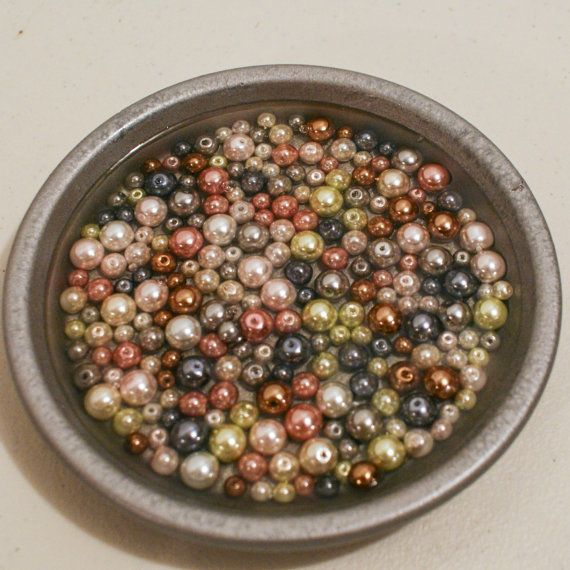 These one-of a kind vibrant 6-inch decorative dishes are designed to hold soaps, car keys, jewelry, or any other keepsake. The beads are all different sizes. They come in vibrant colors of pink, green, yellow, blue, white, and black. Another dish contains pearls in a more muted color embedded in a silver dish. They also appear to be floating in water, but it's really epoxy. Beaded Soap/Jewelry Dish by Timeout4me on Etsy, $12.00.