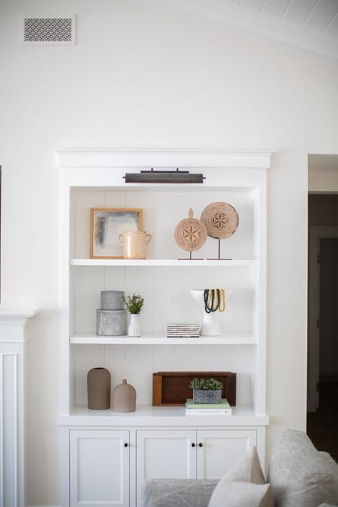 An Oil Rubbed Bronze Picture Light Illuminates White Built In Shelves Accented With A Shiplap In 2020 Bookshelves In Living Room Bookcase Decor Beach House Living Room