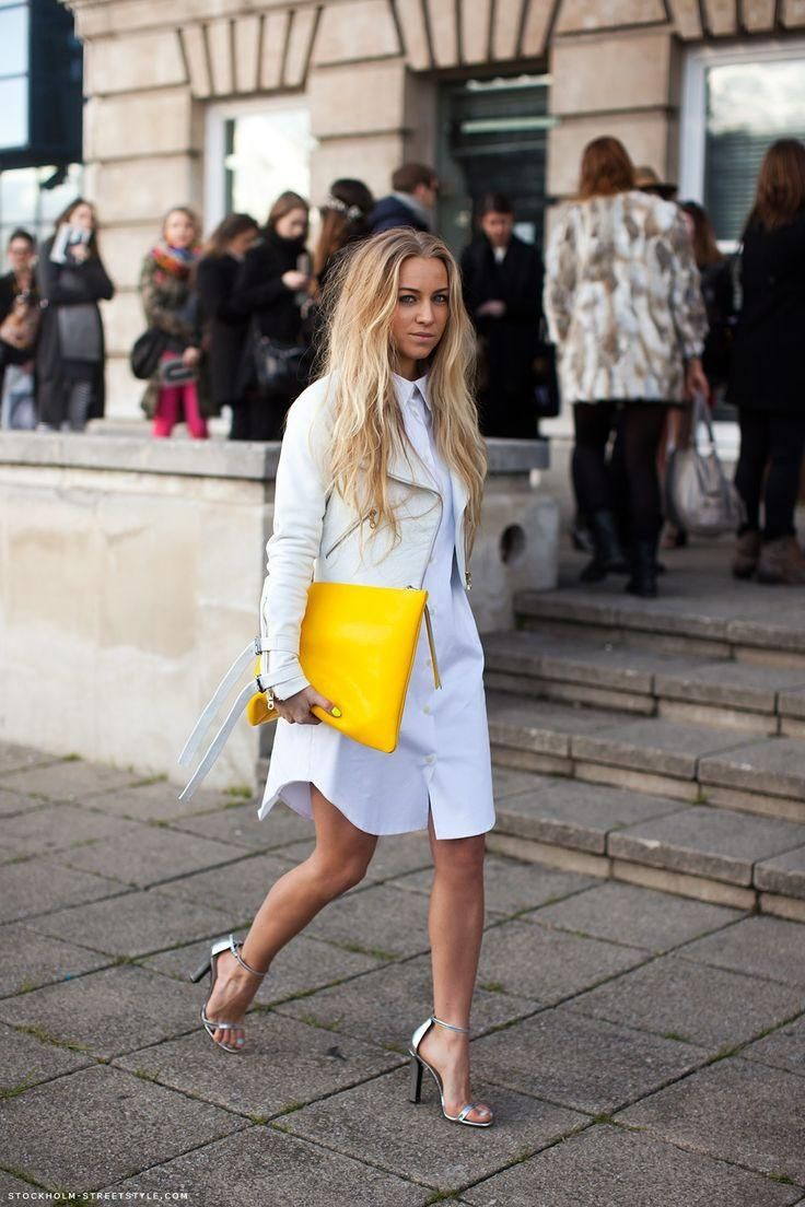 25 Shirtdress Outfit Ideas for Spring - a crisp white shirtdress styled with a white leather jacket, silver metallic ankle strap heels, and a yellow oversized clutch | StyleCaster