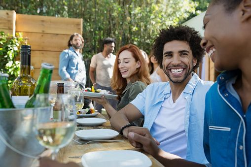 Stock Photo : Friends laughing eating and drinking at patio table