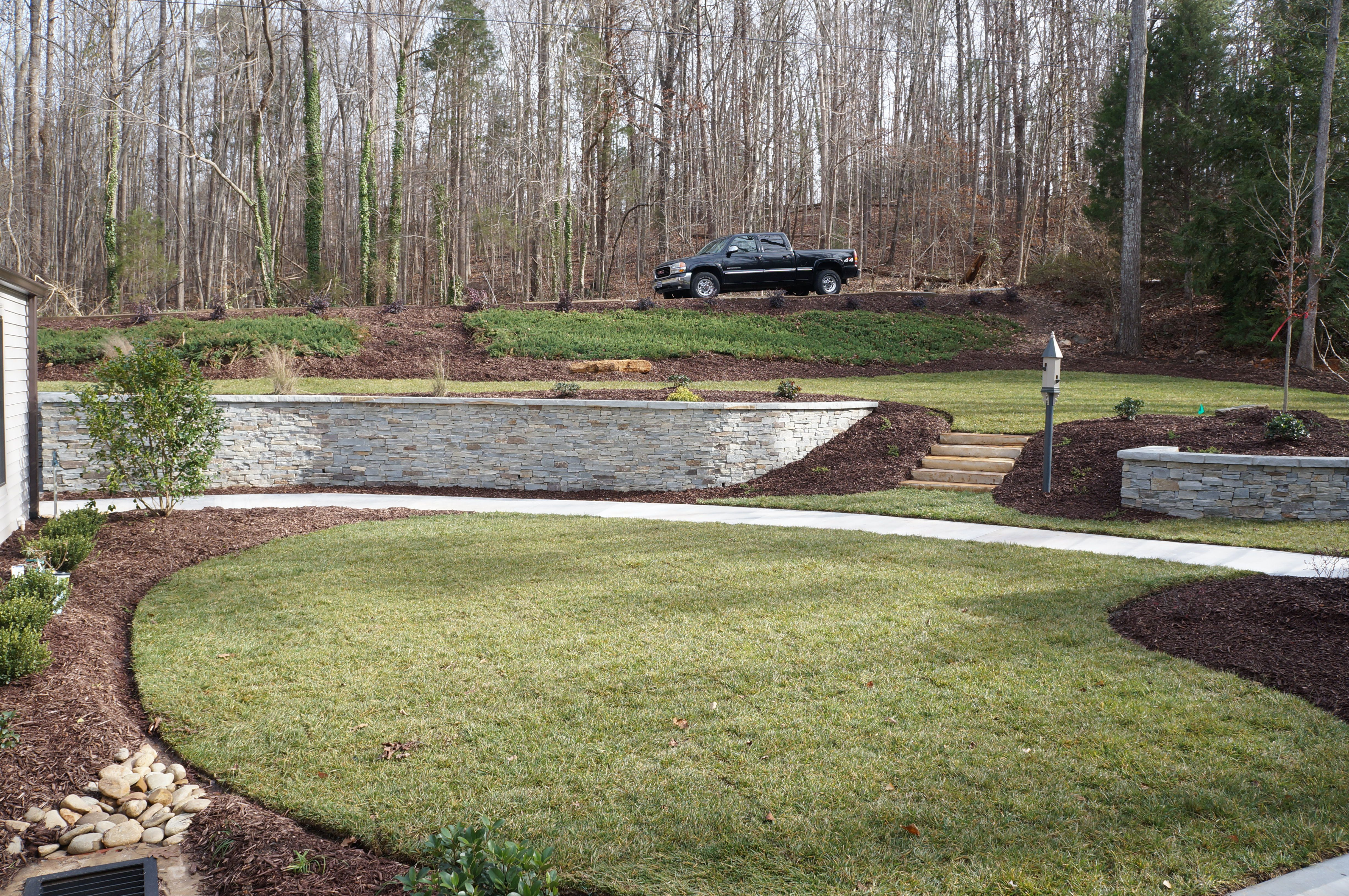 real rock retaining wall the front yard at this home sloped