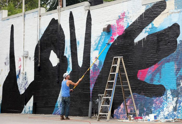 Artist Michael Owen paints a mural on the side of Plan B nightclub ...