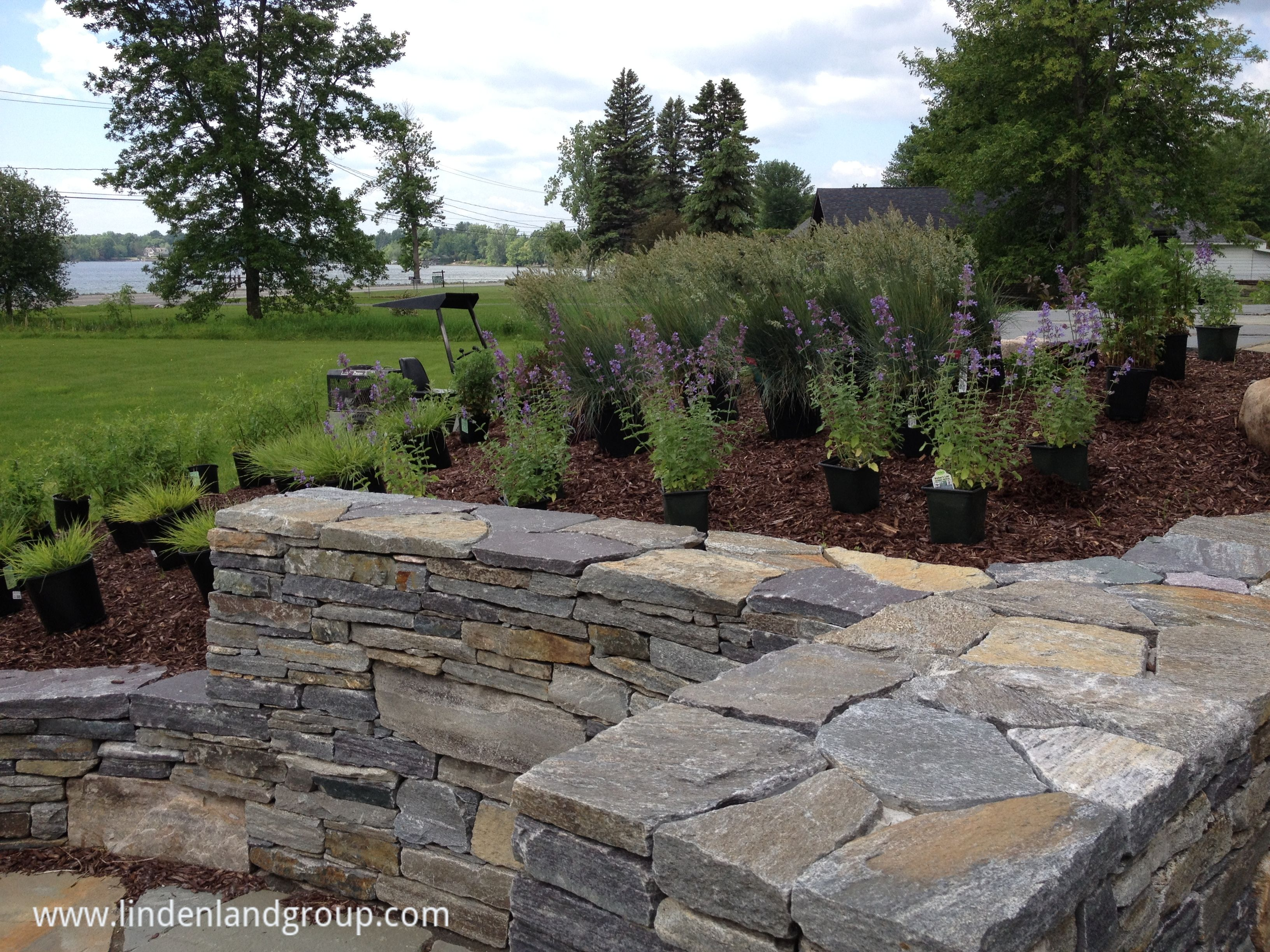 An American Granite Retaining Wall At One Of Our Projects In Chazy Ny Drought Tolerant Plant Sustainable Landscaping Natural Stone Wall Landscape Contractor