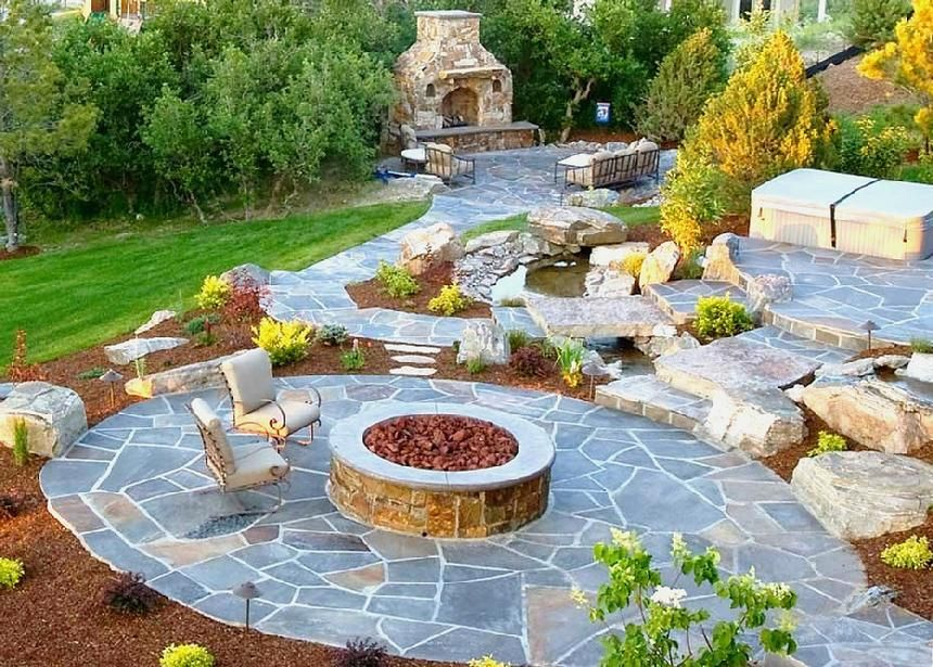 Fire pit with bridges leading over waterfall to sunken hot ...