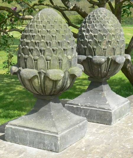 A Pair Of Antique Sandstone Finials Carved As Stylised Pine Cones On Square  Tapered Bases.