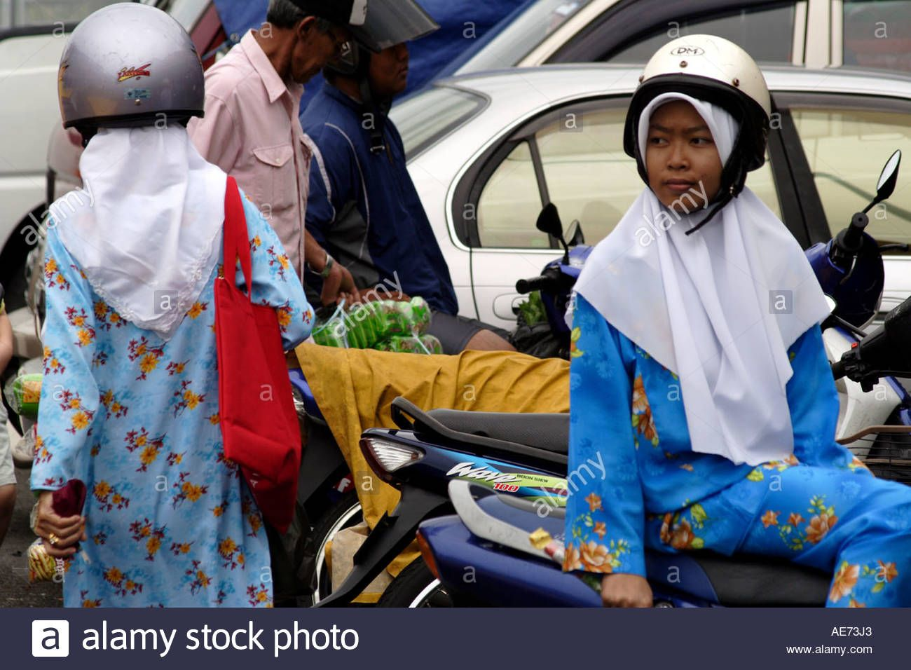 Stock Photo Muslim Women With Motorcycle Helmets Over Traditional Head Cover Outside The Market Kuc Muslim Women Motorcycle Helmets Cool Motorcycle Helmets