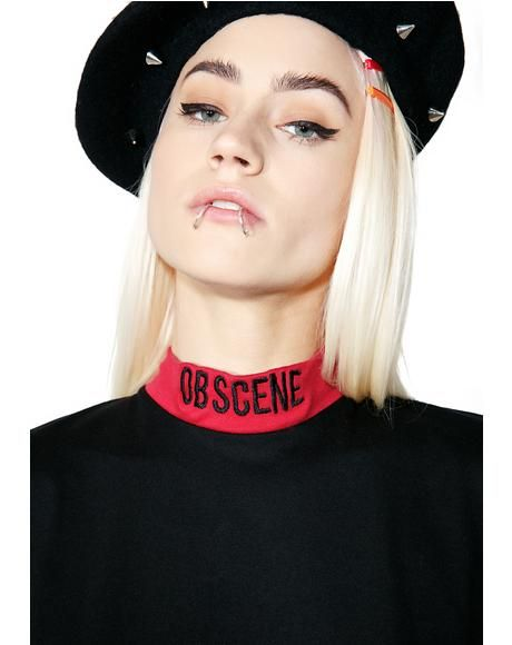 The Ragged Priest Obscene Dress ...did I mislead you at some point, bb? Show 'em yer true self in this dope mini dress, featurin' a swingy black construction, dropped waist, ruffled hemline, cropped sleeves, red banding, and mock neck with embroidery across the front reading 'OBSCENE.'