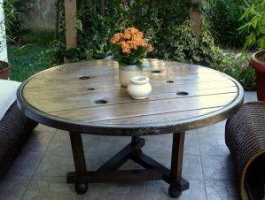 Une grande table basse ronde, en bois et cerclage de métal ...