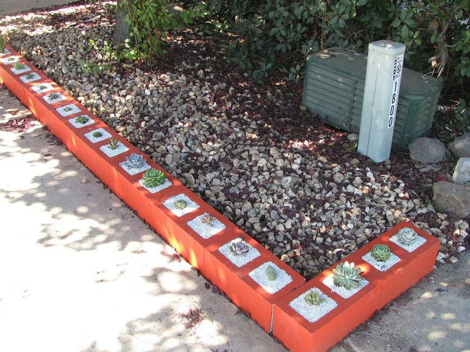 Painted cinder block landscaping border with succulents for Concrete block landscaping ideas