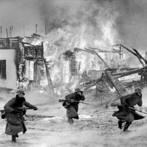3 German soldiers running through a burning Norwegian village. April 1940